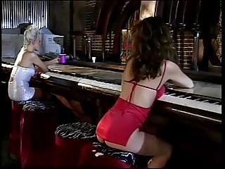 Gorgeous blonde lesbian accosts sexy brunette in red then fucks her with strapon